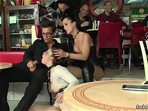 mistress in leather dominates sub in public