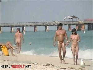 An enormously alluring bare beach voyeur video